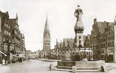 Historische Aufnahme vom Lüneburger Platz AM SANDE; im Vordergrund der Reichenbachbrunnen mit Tränken - im Hintergrund die St. Johanniskirche. Der Platz ist von historischen Giebelhäusern gesäumt.