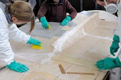 Laminieren beim Bootsbau - Epoxidharz wird auf der aufgebrachten Glasfasermatte mit dem Spachtel verteilt und angedrückt.