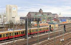 Einfahrender S-Bahnzug in der Haltestelle Beusselstrasse - im Hintergrund Industriearchitektur im Berliner Westhafen.