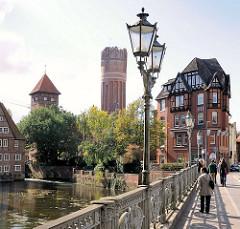 Blick von der Altenbrückertorstrasse in Lüneburg über die Ilmenau; Kandelaber / Laternen auf der Brücke - lks. der Wasserturm und die Ratsmühle.