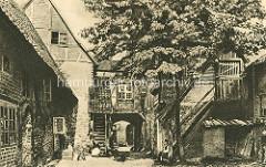 Alter Hinterhof - historische Architektur von Lüneburg; eine Frau sitzt in der Sonne auf der Holztreppe / Mann mit Pfeife - Roter Hahn ca. 1900.