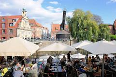 Restaurant unter Sonnenschirmen am Hafen von Lüneburg - im Hintergrund die Barockfassade vom Alten Kaufhaus und der Alte Kran am Hafenkai.