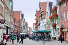 Geschäfte in der Grapengiesserstrasse von Lüneburg - historische Hausfassaden, Blumenkästen mit roten Geranien - Strassencafé, Restaurant unter Sonnenschirmen / Passanten.
