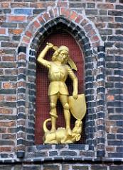 Goldene Figur St. Georg mit Drachen - Nordfassade vom Kämmereiflügel des Lüneburger Rathauses.