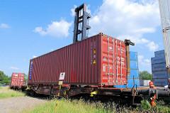 Beladen eines Containerzugs in Hamburg Wilhelmsburg - der Schwerlaststabler senkt den Container auf den Flachwagen - die Stahlbox rastet in den Halterungen ein; der Mitarbeiter dirigiert den Staplerfahrer in die richtige Position..