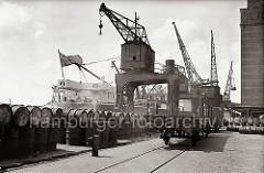 Ein britischer Frachter hat am West Kai vor dem Kühlhaus Neumühlen fest gemacht - über Portalkräne wird die Ladung gelöscht. Auf dem Kai sind Fässer gestapelt, auf der Gleisanlage stehen Güterwaggons der Hafenbahn.