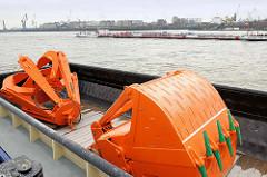 Unterschiedliche Greifer für den HPA-Bagger MODI liegen in einer Schute - auf der Elbe fährt ein Tankschiff.