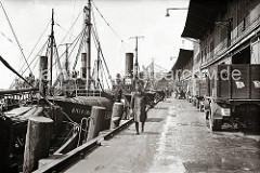 Fischdampfer liegen am Kai des Fischereihafens Altona - vor den Hafenschuppen stehen LKW, auf der Ladefläche sind Fischkisten gestapelt. Ein Kleinlaster mit drei Rädern, eine Art Motorrad mit einer vorderen Ladefläche transportiert Kisten.