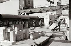 Holzkisten in unterschiedlichen Grössen sind auf der Laderampe gestapelt - eine der Kisten wird mit der Handkarre in das Lagerhaus gebracht, eine weitere Transportkiste hängt am Haken des Halbportalkrans.