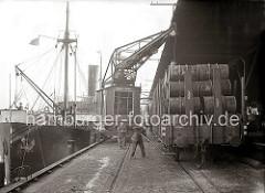 Ein auf Schienen laufender Hafenkran lädt Fässern auf einen Güterzug, der an der überdachten Rampe des Kaischuppens steht.