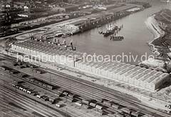 Luftfoto vom Windhukkai des Süd-West-Hafens,  dem Lagerschuppen 59  mit den Tonnengewölben am Veddeler Damm und den Gleisanlagen des Güterbahnhofs Hamburg Süd. Ein Frachter liegt an den Dalben in der Mitte des Hafenbeckens.