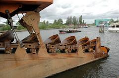 Stahleimer der Endloskette des Kettenbaggers Heimdall im Hafen Harburgs - Arbeitsschiff der Hamburg Port Authority HPA. Im Hintergrund das Gebäude des Wasserschutzkommissariat WSPK 3 am Harburger Überwinterungshafen.