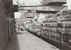 Ein Güterzug wird mit dem Rohstoff Kork im Hamburger Hafen beladen; die Rinde der Korkeiche wird hoch auf den offenen Güterwaggons an der Rampe gestapelt. Ein Kaiarbeiter fährt eine Sackkarre mit einer Fuhre Kork an den Waggon heran.