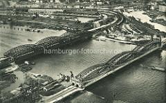 Historische Luftaufnahme von den Hamburger Elbbrücken und der Freihafen-Elbrücke; im Vordergrund das Elbufer in Hamburg Veddel und auf der gegenüberliegenden Elbseite re. der Billehafen und lks. der Kirchenpauerkai sowie der Baakenhafen.