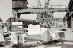 """Kisten werden auf den Anhängern eines Elektrokarrens auf die Laderampe gebracht. Eine grosse Holzkiste steht auf der Laderampe; auf ihrer Seite ist der Zielort """"Winnipeg / Canada"""" und """"Made in Germany"""" gedruckt."""