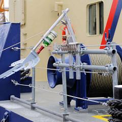 Taufe des Hafenbaggers MODI im Hamburger Hafen - die Sektflasche bewegt sich Richtung Bordwand des Arbeitsschiffs.