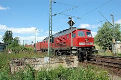 Güterzug mit Containern in Hamburg Wilhelmsburg - im Vordergrund ein alter Holz Prellbock.
