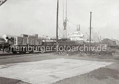 Auf den Gleisen der Hamburger Hafenbahn stehen zwei hoch mit Kisten beladene offene Güterzüge; am Kai sind die Aufbauten eines Frachtschiffs zu erkennen. Im Vordergrund hängt der Haken eines Krans.