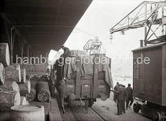 Vor der Rampe des Kaischuppens steht ein voll beladener offener Güterwaggon - Kaiarbeiter sind dabei die Ladung mit einer Plane abzudecken. Auf der Laderampe sind dicke Baumstämme gestapelt und Fässer abgestellt.
