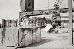 Ein mit Kisten und Stühlen hochbeladener Güterzug steht an einer Laderampe - der die Eisenbahnwaggons werden entladen; ein Arbeiter transportiert mit einer Sackkarre eine grosse Holzkiste zum Lagerschuppen.