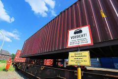 Der Container wird auf den Güterwaggon abgesenkt - Schild Vorsicht privater Bahnübergang.