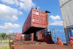 Ein Schwerlaststabler / Gabelstabler transportiert einen Container vom Containerlager zum Güterzug. Langsam wird der Container auf den Flachwagen. Mitarbeiter dirigieren den Fahrer, damit der Container in die im Vordergrund ersichtlichen Halterungen