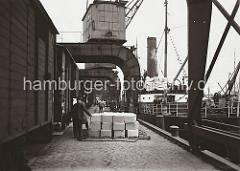 Eine Hieve Pappkartons, die mit einem Netz zusammen gehalten werden, bringt einer der Hafenkrane an Land. Im Vordergrund liegt ein Stapel Kartons auf dem Hafenkai und soll von den Arbeitern in den bereit stehenden Güterwaggon eingeladen werden.