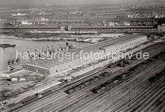 Luftfoto vom Windhukkai des Süd - West - Hafens,  dem Lagerschuppen 59  mit den Tonnengewölben am Veddeler Damm und den Gleisanlagen des Güterbahnhofs Hamburg Süd - der Togo Kai ist noch nicht befestigt. Dahinter stehen Güterwaggons auf den Gleis