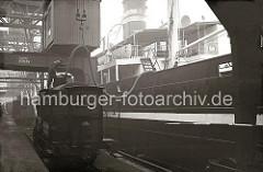 Über einen Kesselwagen der Hamburger Hafenbahn werden mit einem dicken Schlauch die Tanks des Frachtschiffs befüllt. Über den Kran wird der Schlauch in seiner Position gehalten, ein Arbeiter kontrolliert den Vorgang.