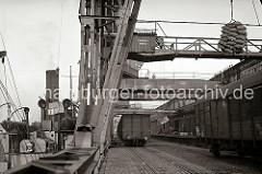 Ein Frachter wird im Hamburger Hafen beladen oder die Ladung wird gerade gelöscht: Hieven mit Säcken und Kiesten schweben an Kranhaken in der Luft. Auf den Gleisen unter den Halbportalkranen stehen Güterwaggons der Hamburger Hafenbahn.