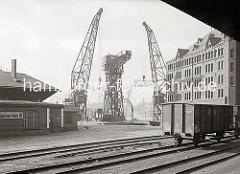 Ein Güterwaggon mit einem schweren Maschinenteil ist über die Drehscheibe auf das Gleis an den Kai des Kaiserhöft gebracht worden. Einer der Schwimmkran hat die Last schon am Haken.