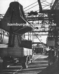 Kohlekai am Altonaer Hafen; Kräne schütten die Kohle in die bereitstehenden Lastwagen -  Hafenarbeiter dirigieren das Schüttgut mit einer langen Stange - im Hintergrund ein Güterwaggon auf den Schienen der Hamburger Hafenbahn; darüber die Förderan
