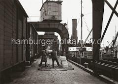 Zwei Hafenarbeiter stehen auf dem Hafenkai in dem auf dem Boden liegenden Transportnetz und laden die an Land gebrachten Kartons von Hand in den Güterwaggon. Im Hintergrund wird gerade eine Ladung Kartons mit einem der Hafenkrane an Land gebracht