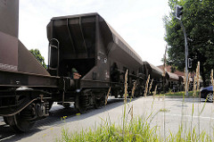 Ein Güterzug mit Schuttgut-Waggons überquert die Versmannstrasse in dem Hamburger Stadtteil Hafencity.