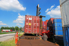 Der Schwerlaststabler senkt den Container auf den Güterzug.