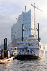 Arbeitsschiff und Fahrgastschiff / Ausflugsschiff im Hamburger Niederhafen - dahinter die Baustelle der Elphilharmonie in der Hamburger Hafencity.