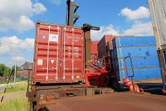 Beladen eines Containerzugs in Hamburg Wilhelmsburg - der Schwerlaststabler senkt den Container auf den Flachwagen - die Stahlbox rastet in den Halterungen ein; der Mitarbeiter dirigiert den Staplerfahrer.