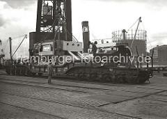 Ein Schwertransport-Güterwagen steht mit einem schweren Maschinenteil auf den Gleisen der Hafenbahn vor dem 150 Tonnen Kran am Kranhöft. Kaiarbeiter sind dabei Drahtseile/ Schwergutstroppen zum Heben der Last vorzubereiten. Auf der anderen Seite