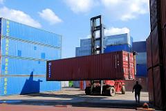 Ein Schwerlaststabler / Gabelstabler transportiert einen Container vom Containerlager zum Güterzug.
