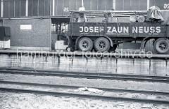 Der Gabelstaplerfahrer hat die Fässer auf der Ladefläche des LKW-Anhängers abgeladen - zwei Arbeiter rollen die Metalltonnen auf dem Anhänger der Spedition Josef Zaun / Neuss, um sie sicher zu verstauen.