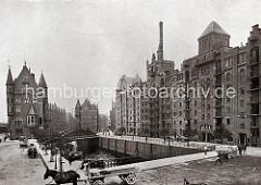 Auf der St. Annenbrücke fahren Pferdefuhrwerke; eines ist mit Säcken beladen; re. die Blöcke Q + R am St. Annenufer, eine Hieve Säcke wird gerade vom Speicherboden auf ein Fuhrwerk herunter gelassen.