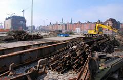 Eisenteile, alte Eisenbahnschienen der Hamburger Hafenbahn - im Hintergrund Blick über den Ericusgraben zur Speicherstadt Hamburgs.