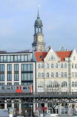 Blick auf den Hamburger Hafenrand / Elbpromenade an den Vorsetzen - die Hochbahn U3 fährt auf dem Bahnviadukt; Bürohaus - Wohnhaus, neu + alt / historische Architektur. Kirchturm der St. Michaeliskirche / Michel; Wahrzeichen der Hansestadt Hamburg.