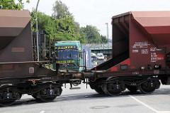 Ein Güterzug mit Schuttgut-Waggons überquert die Versmannstrasse in dem Hamburger Stadtteil Hafencity - Lastwagen müssen warten.