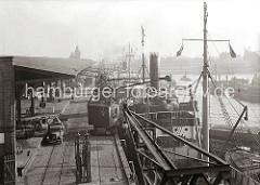 Blick auf hinteren Abschnitt des Baakenhafen mit dem Schuppen 25 am Versmannkai. Ein Rollkran belädt einen Frachter mit Ballen - Kaiarbeiter bereiten auf der Laderampe den Transport weiterer Güter vor.
