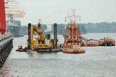 Hafenbagger baggern das Hafenbecken Waltershofer Hafen - das Baggergut wird in Schuten verladen.