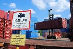 Ein Schwerlaststabler / Gabelstabler transportiert einen Container vom Containerlager zum Güterzug. Schild Vorsicht privater Bahnübergang.