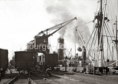 Ein Frachter liegt an der Kaimauer des Holthusenkais in der Norderelbe - über einen Portalkran wird das Schiff mit Säcken beladen. Auf den Gleisen der Bahnanlage stehen die Güterwaggons von denen die Fracht auf das Frachtschiff geladen wird