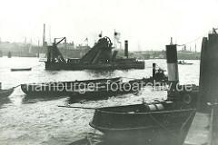 Historischer Bagger beim ausbaggern der Elbe vor Hamburg - im Vordergrund ein Tauchschiff.