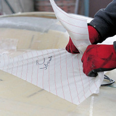 Abziehen des Glasfasergewebe nach dem Laminieren des Bootes.